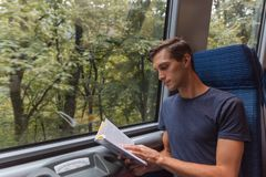 Młody przystojny mężczyzna czyta książkę podczas gdy podróżujący pociągiem obrazy royalty free
