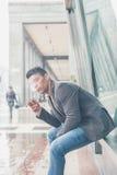 Młody przystojny mężczyzna dymi papieros Fotografia Stock
