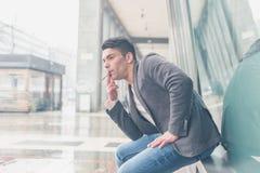 Młody przystojny mężczyzna dymi papieros Obraz Royalty Free