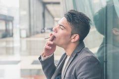 Młody przystojny mężczyzna dymi papieros Zdjęcia Stock