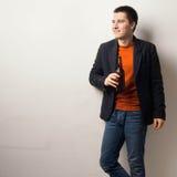 Młody przystojny mężczyzna pije piwo od szklanej butelki Fotografia Stock