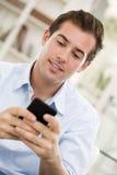 Młody przystojny mężczyzna pisze SMS na telefonie komórkowym. obraz stock