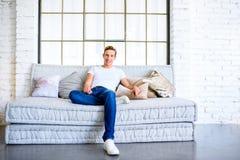 Młody przystojny mężczyzna relaksuje na kanapie w loft stylu apartm zdjęcie royalty free