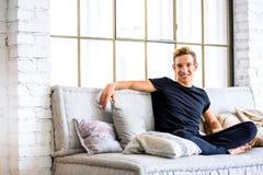 Młody przystojny mężczyzna relaksuje na kanapie w loft stylu apartm obraz stock
