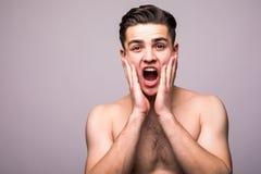 Młody przystojny mężczyzna stosuje aftershave twarzy śmietankę odizolowywającą na szarym tle Obrazy Royalty Free