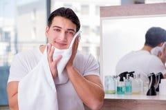 Młody przystojny mężczyzna stosuje twarzy śmietankę Fotografia Stock