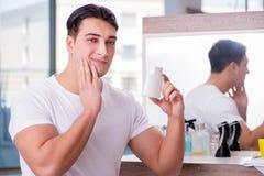 Młody przystojny mężczyzna stosuje twarzy śmietankę Zdjęcia Stock