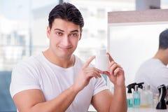 Młody przystojny mężczyzna stosuje twarzy śmietankę Zdjęcie Royalty Free