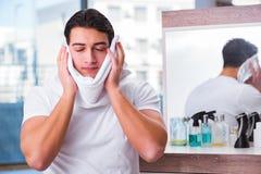 Młody przystojny mężczyzna stosuje twarzy śmietankę Obrazy Royalty Free