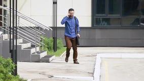 Młody przystojny mężczyzna ubierający w błękitnej przypadkowej koszula i brown spodniach kroczy outside od budynku mówienia na zdjęcie wideo