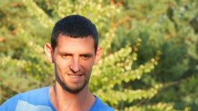 Młody przystojny mężczyzna w błękitnej pasiastej koszulce łapie trutnia lub quadrocopter zdjęcie wideo