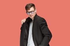 Młody przystojny mężczyzna w czarnym kostiumu i szkłach odizolowywających na czerwonym tle Zdjęcie Stock