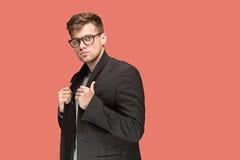 Młody przystojny mężczyzna w czarnym kostiumu i szkłach odizolowywających na czerwonym tle Fotografia Stock