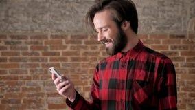 Młody przystojny mężczyzna z brodą ogląda fotografie na jego smartphone, komunikacyjny pojęcie, ceglany tło zbiory wideo