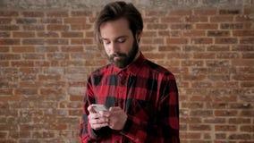Młody przystojny mężczyzna z brodą pisać na maszynie wiadomości na jego smartphone, komunikacyjny pojęcie, ceglany tło zbiory