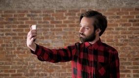 Młody przystojny mężczyzna z brodą robi selfie na jego smartphone, komunikacyjny pojęcie, ceglany tło zbiory