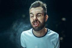 Młody przystojny mężczyzna z brody kichnięciem, pracowniany portret obraz stock