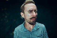 Młody przystojny mężczyzna z brody kichnięciem, pracowniany portret zdjęcie stock