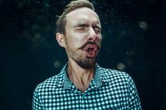 Młody przystojny mężczyzna z brody kichnięciem, pracowniany portret obraz royalty free