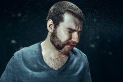 Młody przystojny mężczyzna z brody kichnięciem, pracowniany portret fotografia stock