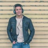 Młody przystojny mężczyzna z hełmofonami pozuje w miasto ulicach Obraz Stock