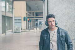 Młody przystojny mężczyzna z hełmofonami pozuje w miasto ulicach Obraz Royalty Free