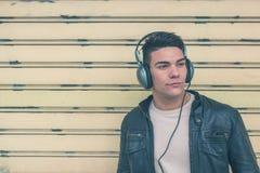 Młody przystojny mężczyzna z hełmofonami pozuje w miasto ulicach Zdjęcie Stock