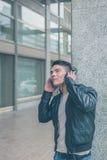 Młody przystojny mężczyzna z hełmofonami pozuje w miasto ulicach Fotografia Stock