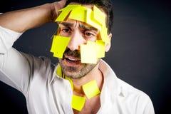 Młody przystojny mężczyzna z kleistymi notatkami na jego twarz zdjęcie stock