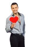 Młody przystojny mężczyzna z sercem kształtował zabawkę odizolowywającą Fotografia Stock