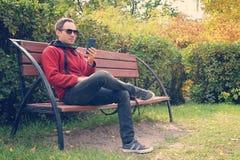 Młody przystojny mężczyzny obsiadanie na ławce patrzeje jego smartphone ekran Facet czyta wiadomość na telefonie zdjęcia stock