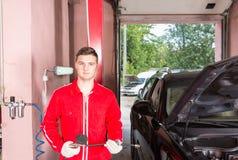 Młody przystojny męski auto mechanika mienia wyposażenie dla sprawdzać Zdjęcia Stock