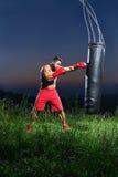 Młody przystojny męski bokser ćwiczy na uderza pięścią torbie outdoors Fotografia Stock