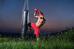 Młody przystojny męski bokser ćwiczy na uderza pięścią torbie outdoors Obrazy Royalty Free
