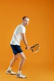 Młody przystojny męski gracz w tenisa bawić się tenisa na żółtym backgro Zdjęcia Royalty Free
