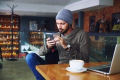 Młody przystojny modnisia mężczyzna z brody obsiadaniem w cukiernianym opowiada telefonie komórkowym, trzymający filiżankę kawy i fotografia royalty free