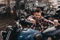młody przystojny motocyklista z klasycznym motocyklem fotografia royalty free