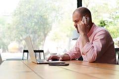Młody przystojny programisty obsiadanie w kawiarni i opowiadać na telefonie Obraz Stock
