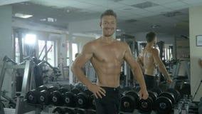 Młody przystojny sportowiec stoi mięśnie i cedzi, demonstrujący pompującego ciała, obraca kłaść jego rękę na zdjęcie wideo
