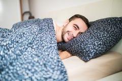 Młody przystojny szczęśliwy mężczyzna budzi się up na łóżku w domu Zdjęcia Stock