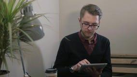 Młody przystojny uśmiechnięty mężczyzna z szkłami ma filiżankę kawy używać pastylkę przy kawiarnią zbiory wideo