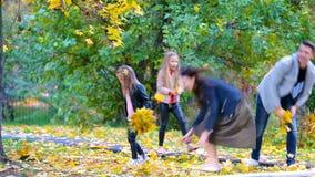 Młody rodzina składająca się z czterech osób rzuca liście wokoło na jesień dniu outdoors zbiory wideo