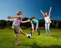 Młody rodzinny bawić się futbol zdjęcie stock