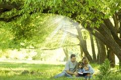 Młody rodzinny czytanie biblia w naturze obrazy royalty free