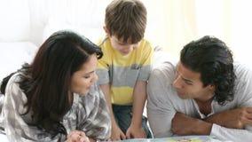 Młody rodzinny czytanie na podłoga zbiory wideo