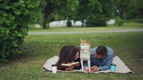 Młody rodzinny wydatki weekend w parku, kobiety czytelnicza książka, mężczyzna używa smartphone, śliczny psi odpoczywać między on zbiory