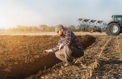 Młody rolnik examing uprawianej banatki podczas gdy ciągnik orze fie Obraz Royalty Free