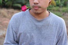 Młody romantyczny mężczyzna trzyma czerwieni róży w jego usta na natura zamazującym tle Miłości i romans walentynki ` s dnia poję Zdjęcie Stock