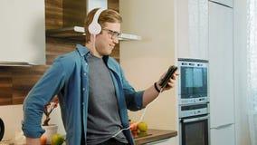 Młody roześmiany mężczyzna dopatrywanie leje się film na cyfrowych pastylki łasowania zbożach z hełmofonami zbiory wideo