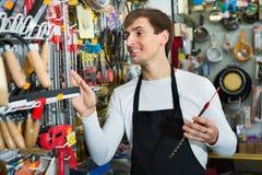 Młody rozochocony życzliwy sprzedawcy działanie, ono uśmiecha się i zdjęcie stock